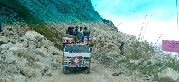 Bus on a washed out road wide enough for one vehicle to pass, Haiti.